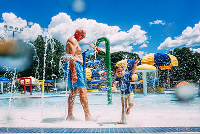 Grandfather looking at granddaughter enjoying in water park - p1166m1489633 by Cavan Images