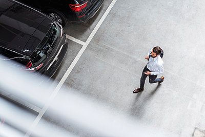 Young businessman with backpack on the go at parking garage - p300m1587951 von Daniel Ingold