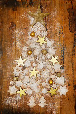 Christmas cookies and golden Christmas baubles and stars forming Christmas Tree on wood - p300m2012565 by Gaby Wojciech
