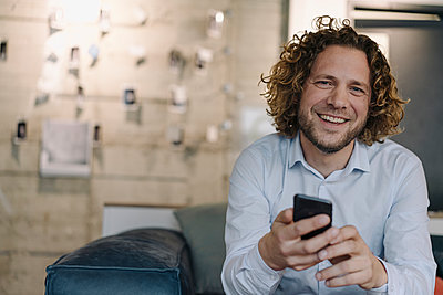 Portrait of happy businessman with cell phone having a break in office - p300m2167335 by Kniel Synnatzschke