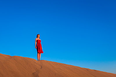 Woman in red dress standing in the dunes under blue sky, Gran Canaria, Spain - p300m2197923 by Daniel Ingold