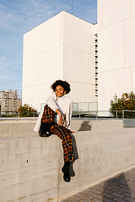 Carefree young woman with afro hair sitting on retaining wall against buildings in city - p300m2256643 by Tania Cervián