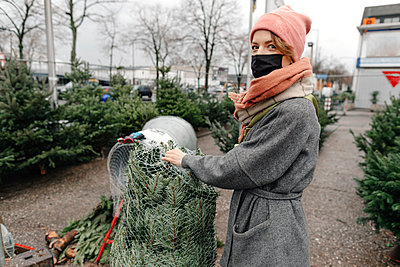 Woman buying Christmas tree from market during COVID-19 - p300m2257018 by Oxana Guryanova