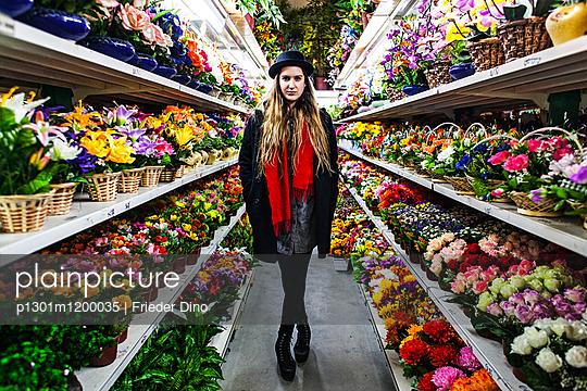 Frau steht in Plastikblumenladen - p1301m1200035 von Delia Baum