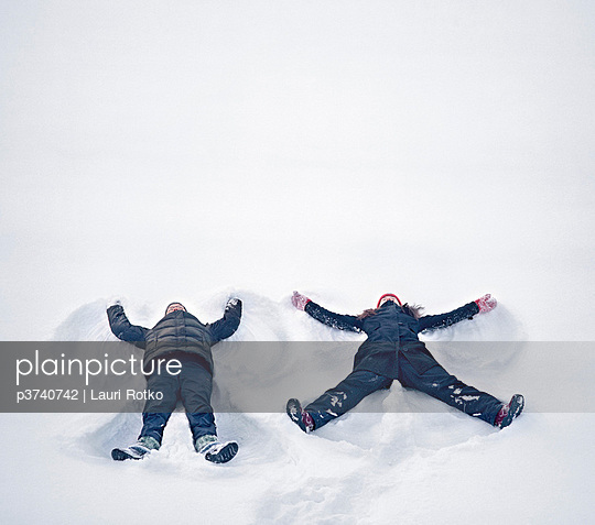 High angle view of two young women making snow angels - p3740742 by Lauri Rotko