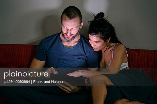 Hipster couple using digital tablet on sofa - p429m2090964 by Frank and Helena