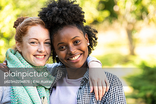 Portrait of smiling young women with arms around - p623m2294876 by Eric Audras