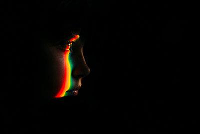 Close-up of spectrum on girl in darkroom - p1166m1524577 by Cavan Images