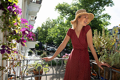 Blonde woman on her balcony - p1678m2258821 by vey Fotoproduction