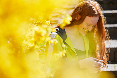 Teenage girl sitting outdoors on steps, checking her mobile phone, yellow Forsythia in foreground. - p429m2200763 by Emma Kim
