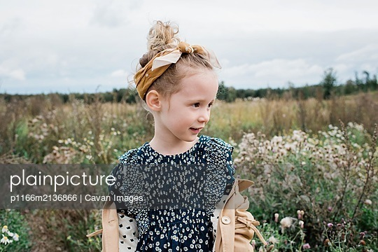 portrait of a pretty young girl stood in a field of wild flowers - p1166m2136866 by Cavan Images