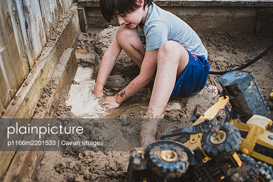Young boy playing in puddle of muddy sandbox filled with toy trucks. - p1166m2201533 by Cavan Images