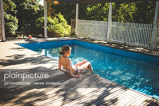 Girl relaxing at swimming-pool - p312m2092086 by Henrik Kindgren