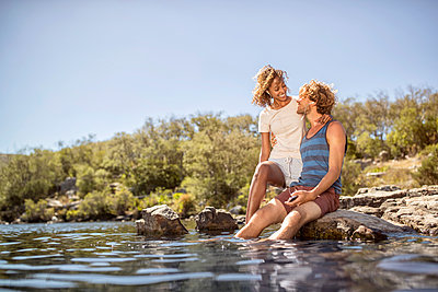 Young couple on the riverbank - p1355m1574519 by Tomasrodriguez
