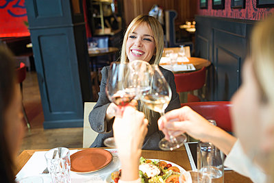 Smiling businesswomen meeting and clinking wine glasses in a restaurant - p300m2140179 by Josep Suria