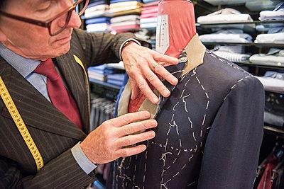 Tailor preparing bespoke suit jacket on tailors dummy - p429m2003686 by G. Mazzarini