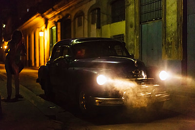Vintage car driving on city street at night - p555m1454130 by Jeremy Woodhouse
