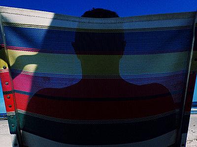 Mann im Liegestuhl am Strand - p988m2015073 von Rachel Rebibo