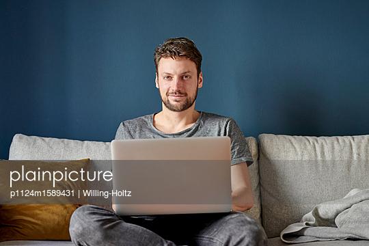 Junger Mann arbeitet am Laptop Computer - p1124m1589431 von Willing-Holtz