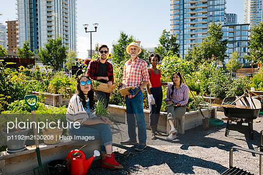Portrait man teaching gardening to young adults in sunny, urban community garden - p1192m2130208 by Hero Images