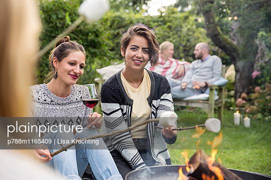 Freunde rösten Marshmallows  - p788m1165409 von Lisa Krechting