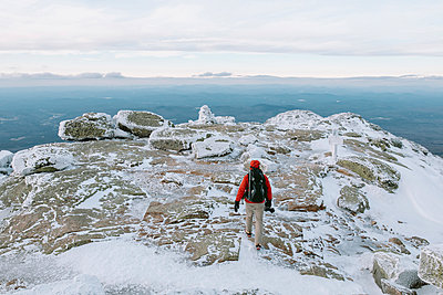 Rear view of backpacker with camera walking on snow covered rocks - p1166m2001279 by Cavan Images