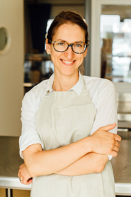 Portrait of female chef in glasses and apron smiling at camera - p1166m2212805 by Cavan Images