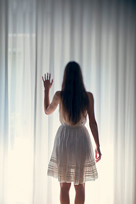 Mystical young woman standing in front of a white curtain, back view - p300m981644f by Biederbick&Rumpf