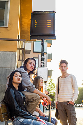 Multiethnic high school students waiting at bus stop - p426m958674f by Maskot