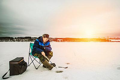 Man ice fishing in frozen lake - p555m1311900 by Aleksander Rubtsov