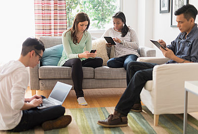 Friends using technology in living room - p555m1413021 by JGI/Tom Grill