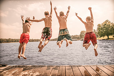 Caucasian boys jumping off wooden dock - p555m1454164 by Jon Feingersh