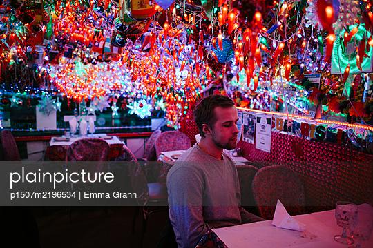 Mann allein in einem Restaurant, bunte Beleuchtung - p1507m2196534 von Emma Grann