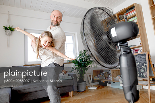 Father playing with cheerful daughter in front of electric fan at home - p300m2256097 by Katharina Mikhrin