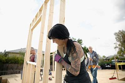 Female volunteer with tattoos helping lift frame, building house - p1192m2024511 by Hero Images
