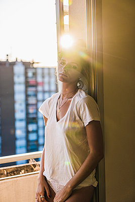 Portrait of young woman standing at the window in backlight - p300m2029721 by Kike Arnaiz