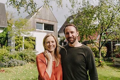Happy couple standing in their garden - p300m2166713 by Kniel Synnatzschke