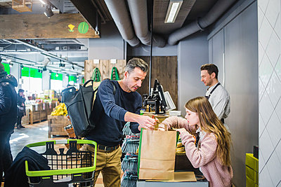 Father and daughter packing groceries in paper bag at checkout counter - p426m2097743 by Maskot