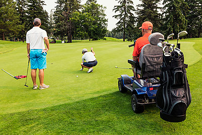 Two able bodied golfers team up with a disabled golfer using a specialized powered golf wheelchair and putting together on a golf green playing best ball; Edmonton, Alberta, Canada - p442m2019730 by LJM Photo