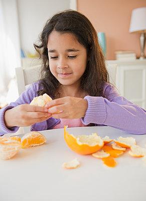 Mixed race girl peeling an orange - p555m1479097 by JGI/Jamie Grill
