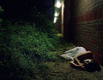 Woman lying by brick wall at night - p9241967 by Iveta Vaivode