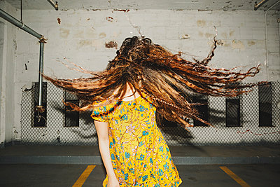 Front view of young woman shaking her long wavy hair in indoor carpark - p924m1180268 by Lena Mirisola