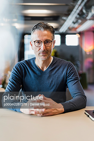 Mature businessman sitting with hands clasped at desk in office - p300m2287278 by Daniel Ingold