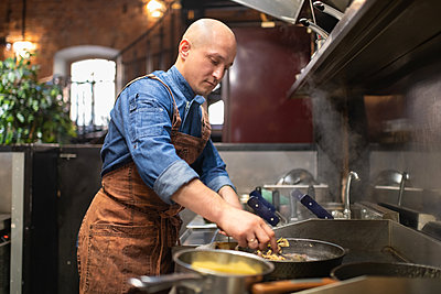 Bald man frying food in cafeteria kitchen - p1166m2250628 by Cavan Images