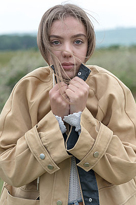 Young woman outdoors clutching her jacket, looking cold or frightened. - p1433m2207470 by Wolf Kettler
