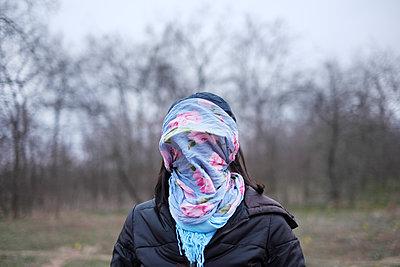 Junge Frau mit einem blauem Schal mit Blumenmotiv über ihrem Gesicht - p1527m2116783 von Slaveng