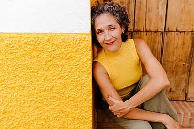 Mature woman smiling while sitting against old door - p300m2221416 by Tania Cervián
