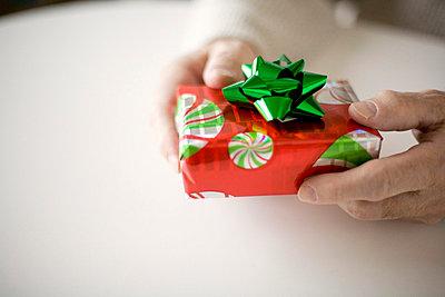 Senior man holding gift, close-up - p3720437 by James Godman