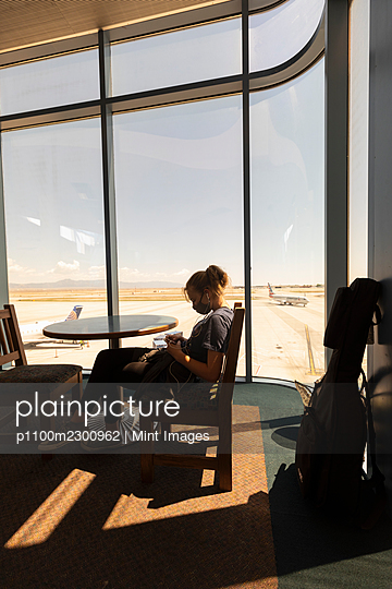 Teenage girl sitting waiting in an airport lounge, on her smart phone, Botswana. - p1100m2300962 by Mint Images