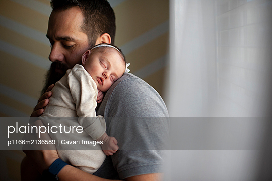 Father embracing sleeping newborn daughter on shoulder at home - p1166m2136589 by Cavan Images